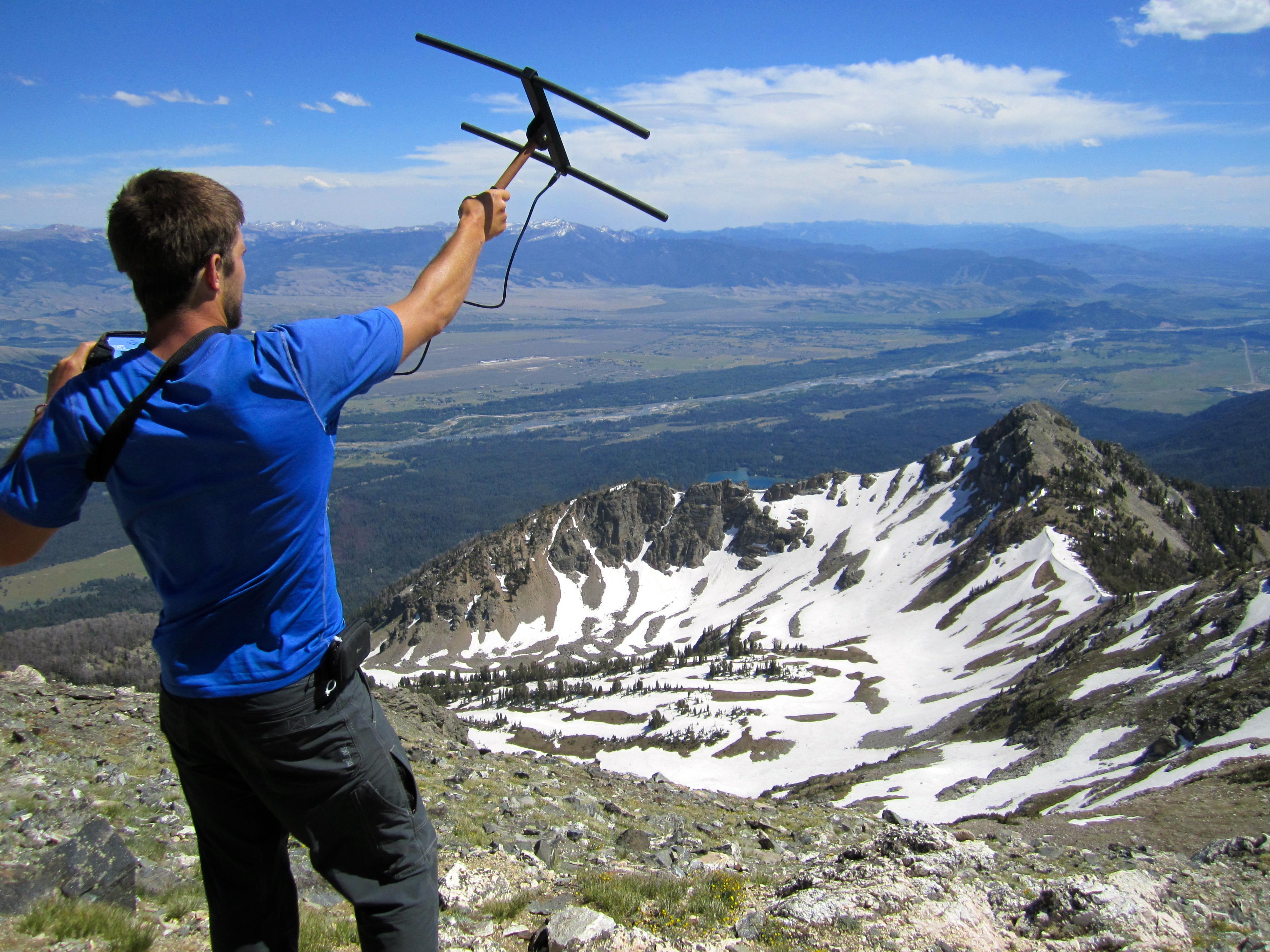 Man holding radio telemetry looking over mountain range